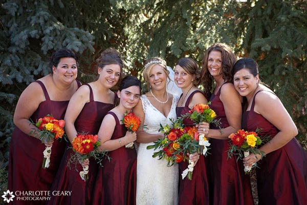 Bridesmaids in red dresses at a fall wedding