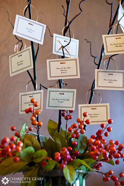 Wedding place cards hung from curly willow branches