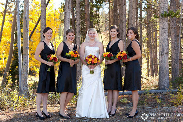 Bridesmaids in black dresses with autumn flowers