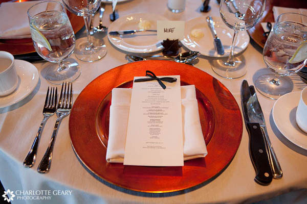 Place setting with an orange charger plate for a fall wedding