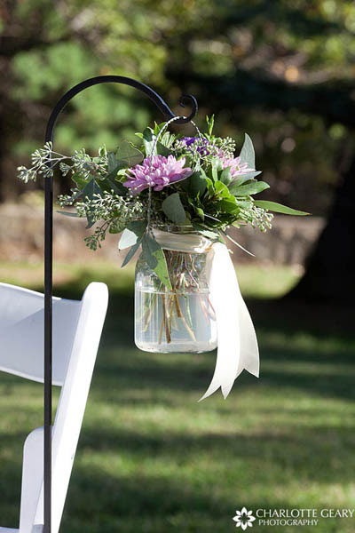 Flower arrangements in mason jars hung from shepherds hooks