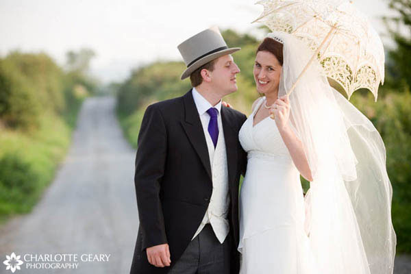 Groom with top hat and bride with lace parasol