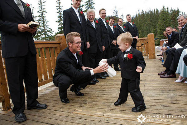 Ring bearer in tuxedo with red boutonniere