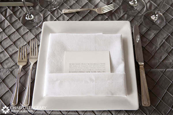 Place setting with square white plates and menu card